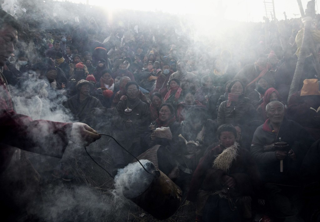 SERTAR, CHINA - NOVEMBER 1: Tibetan Buddhist nomads are blessed with juniper smoke as they pray at the annual Bliss Dharma Assembly at the Larung Wuming Buddhist Institute on November 1, 2015 in Sertar county, in the remote Garze Tibetan Autonomous Prefecture, Sichuan province, China. The last of four annual assemblies, the week long annual gathering takes place in the ninth month of the Tibetan calendar and marks Buddha's descent from the heavens. Located high in the mountains of Sichuan, the Larung Wuming Buddhist Institute was founded in 1980 by an influential lama of the Nyingma sect and is widely regarded as the world's largest and most influential centres for Tibetan Buddhist studies. The school is home to thousands of monks and nuns and is popular for followers from all over the Tibetan areas and other parts of China. (Photo by Kevin Frayer/Getty Images)