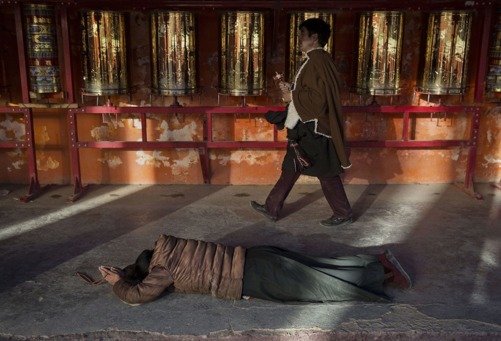 SERTAR, CHINA - NOVEMBER 1: A Tibetan Buddhist woman prostrates at a monastery above the annual Bliss Dharma Assembly at the Larung Wuming Buddhist Institute on November 1, 2015 in Sertar county, in the remote Garze Tibetan Autonomous Prefecture, Sichuan province, China. The last of four annual assemblies, the week long annual gathering takes place in the ninth month of the Tibetan calendar and marks Buddha's descent from the heavens. Located high in the mountains of Sichuan, the Larung Wuming Buddhist Institute was founded in 1980 by an influential lama of the Nyingma sect and is widely regarded as the world's largest and most influential centres for Tibetan Buddhist studies. The school is home to thousands of monks and nuns and is popular for followers from all over the Tibetan areas and other parts of China. (Photo by Kevin Frayer/Getty Images)