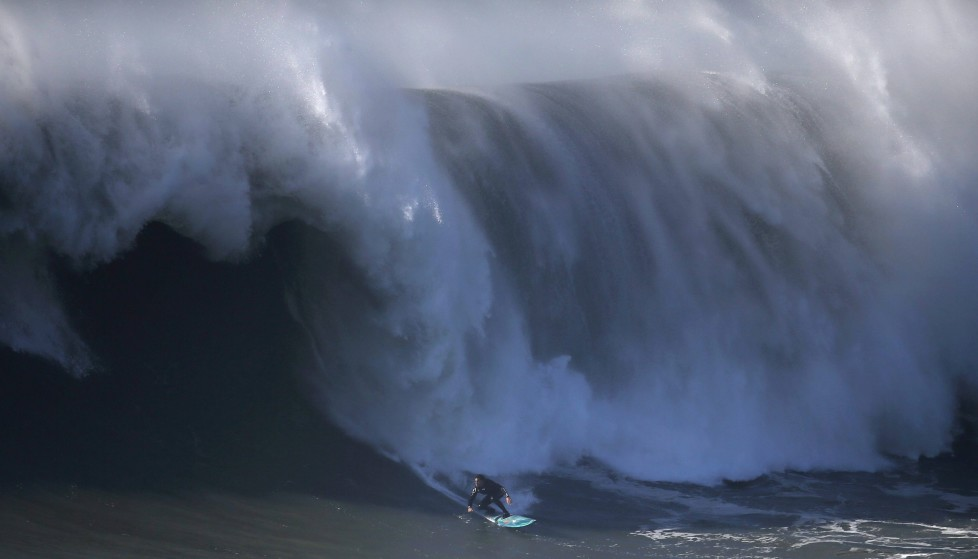Portuguese surfer Alex Botelho drops in on a large wave at Praia do Norte in Nazare, Portugal November 29, 2015. The Praia do Norte beach has become a famous beach for big waves surfers around the world since Hawaiian surfer Garrett McNamara's world record for the largest wave surfed in 2011. REUTERS/Rafael Marchante