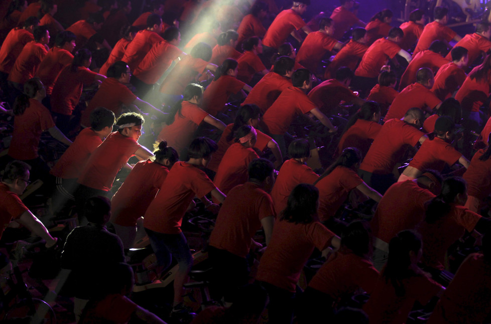 A participant is seen under a beam of light as hundreds of people ride indoor bicycles during a campaign to promote body-building exercises, at a gymnasium in Kunming, Yunnan province, China, December 1, 2015. Picture taken December 1, 2015. REUTERS/Wong Campion TPX IMAGES OF THE DAY - RTX1WRB9