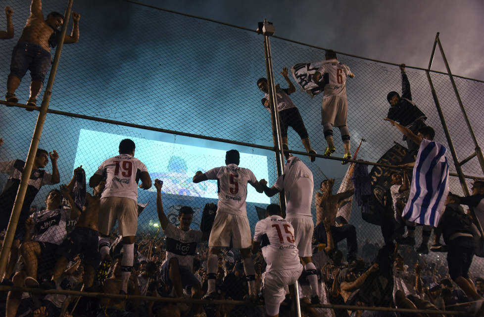 Olimpia's players celebrate after defeating Cerro Porteno 2 -1 to win the Clausura football tournament, at the Defensores del Chaco stadium in Asuncion, on December 9, 2015. / AFP / NORBERTO DUARTE