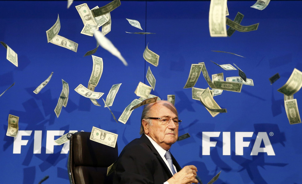 British comedian known as Lee Nelson (unseen) throws banknotes at FIFA President Sepp Blatter as he arrives for a news conference after the Extraordinary FIFA Executive Committee Meeting at the FIFA headquarters in Zurich, Switzerland July 20, 2015. World football's troubled governing body FIFA will vote for a new president, to replace Sepp Blatter, at a special congress to be held on February 26 in Zurich, the organisation said on Monday. REUTERS/Arnd Wiegmann TPX IMAGES OF THE DAY FOR BEST QUALITY IMAGE ALSO SEE: GF10000187908 - RTX1L1TH