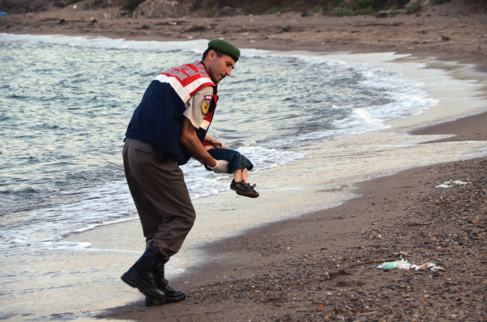 JAHRESRUECKBLICK 2015 - MIGRATION - A paramilitary police officer carries the lifeless body of Aylan Kurdi, 3, after a number of migrants died and a smaller number were reported missing after boats carrying them to the Greek island of Kos capsized, near the Turkish resort of Bodrum early Wednesday, Sept. 2, 2015. The family — Abdullah, his wife Rehan and their two boys, 3-year-old Aylan and 5-year-old Galip — embarked on the perilous boat journey only after their bid to move to Canada was rejected. The tides also washed up the bodies of Rehan and Galip on Turkey's Bodrum peninsula Wednesday, Abdullah survived the tragedy. (AP Photo/DHA) TURKEY OUT