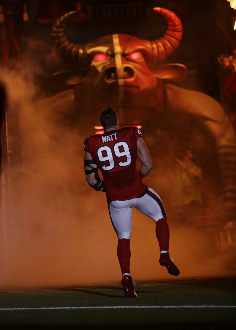 Houston Texans defensive end J.J. Watt (99) spins as he runs out of the tunnel before an NFL football game against the New England Patriots, Sunday, Dec. 13, 2015, in Houston. (AP Photo/David J. Phillip)