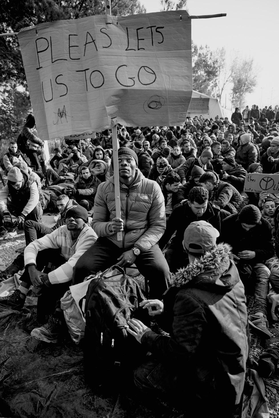 Flüchtlinge die im Camp in Idomeni festsitzen , wenn sie nicht aus Syrien, Afgahnistan oder dem Irak stammen . Menschen protestieren friedlich gegen das aufgehlaten werden mit Kartonschildern . Zu dem Zeitpunkt war die gesamte Balkanroute geschlossen .