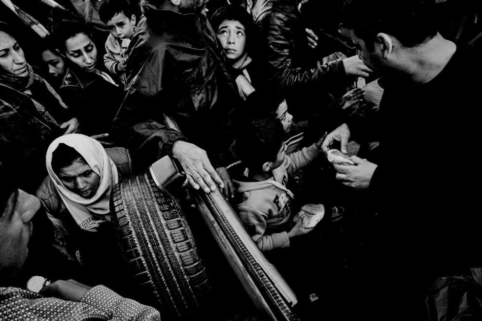 Im Hafen von Mitilini. Flüchtlinge warten auf die Fähre zum Festland. Dichtes gedrängen um einen Freiwilligen der Brot verteilt.