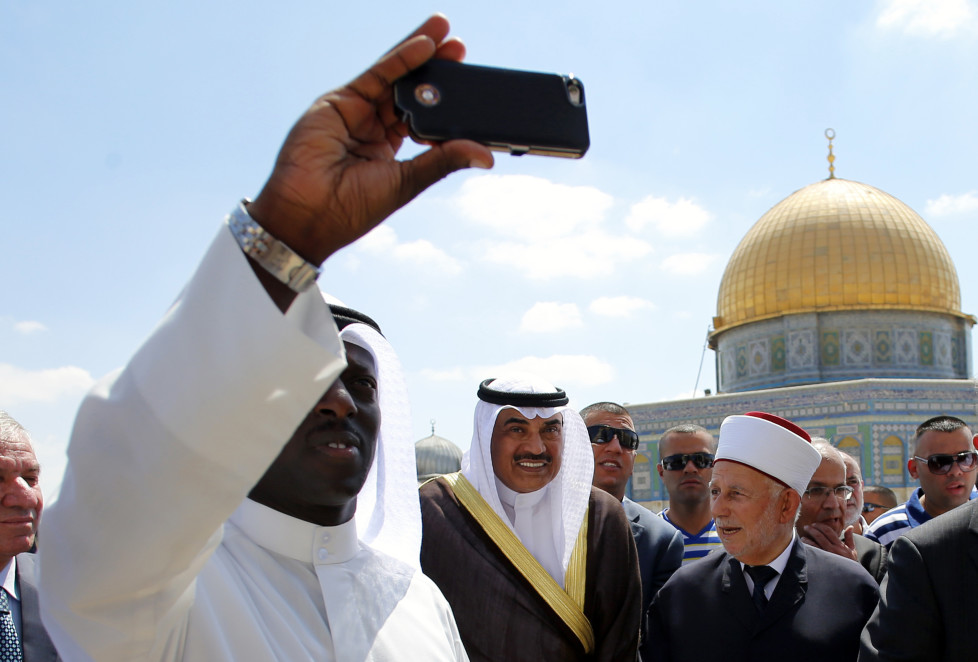 """Kuwaiti Foreign Minister Sheikh Sabah al Khalid al-Sabah's (C) poses for a """"selfie"""" with a member of his delegation in front of the Dome of the Rock during a visit at the compound known to Muslims as Noble Sanctuary and to Jews as Temple Mount in Jerusalem's Old City September 14, 2014. REUTERS/Ammar Awad (JERUSALEM - Tags: POLITICS RELIGION) - RTR465GQ"""