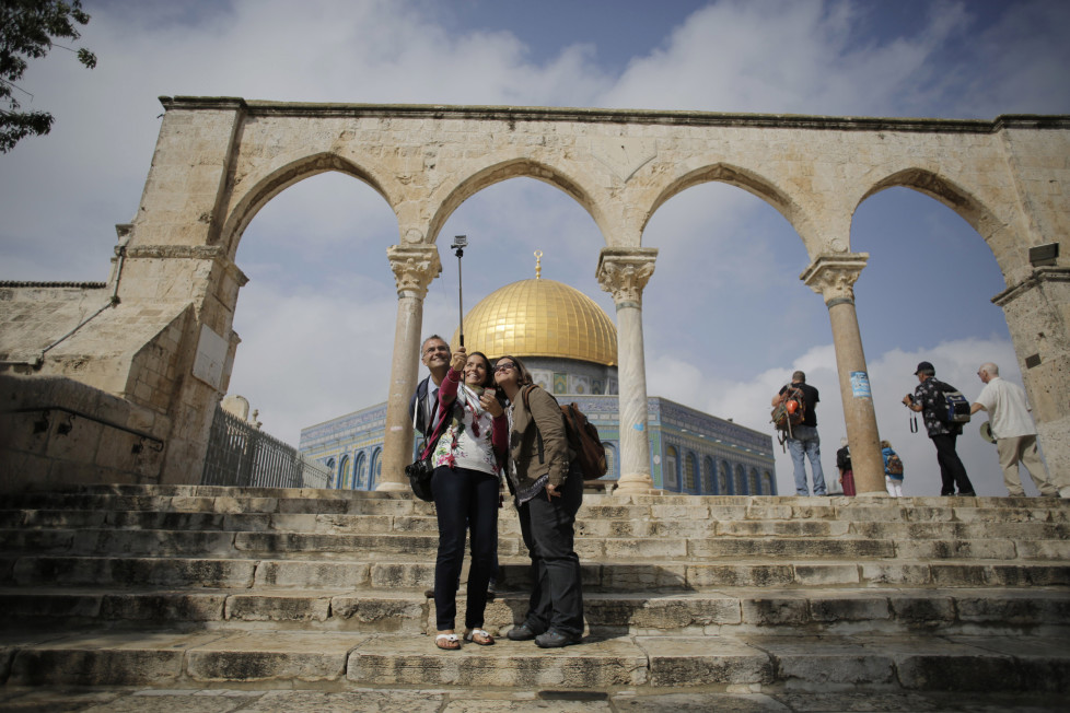 Tourists pose for a selfie in front of the Dome of the Rock on the compound known to Muslims as Noble Sanctuary and to Jews as Temple Mount, in Jerusalem's Old City October 19, 2014. Clashes have flared repeatedly in the past few weeks as increasing numbers of Jews have visited the sacred area during the Jewish holidays, angering Palestinians who see this as part of an Israeli agenda to alter a long-preserved status quo. REUTERS/Ammar Awad (JERUSALEM - Tags: RELIGION CIVIL UNREST POLITICS) - RTR4AQFN