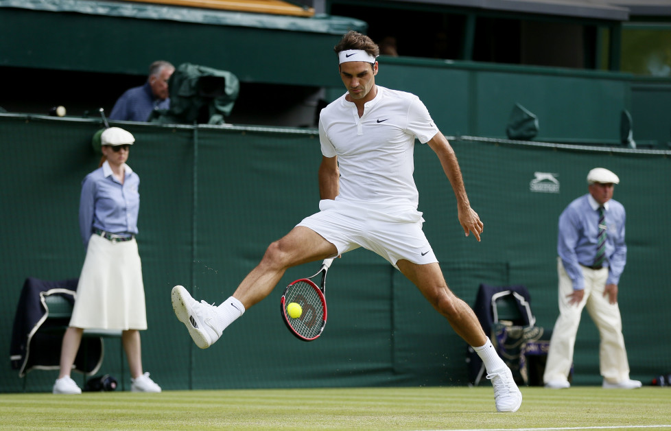 Roger Federer of Switzerland hits a shot through his legs during his match against Sam Querrey of the U.S.A. at the Wimbledon Tennis Championships in London, July 2, 2015. REUTERS/Stefan Wermuth - RTX1IS6E