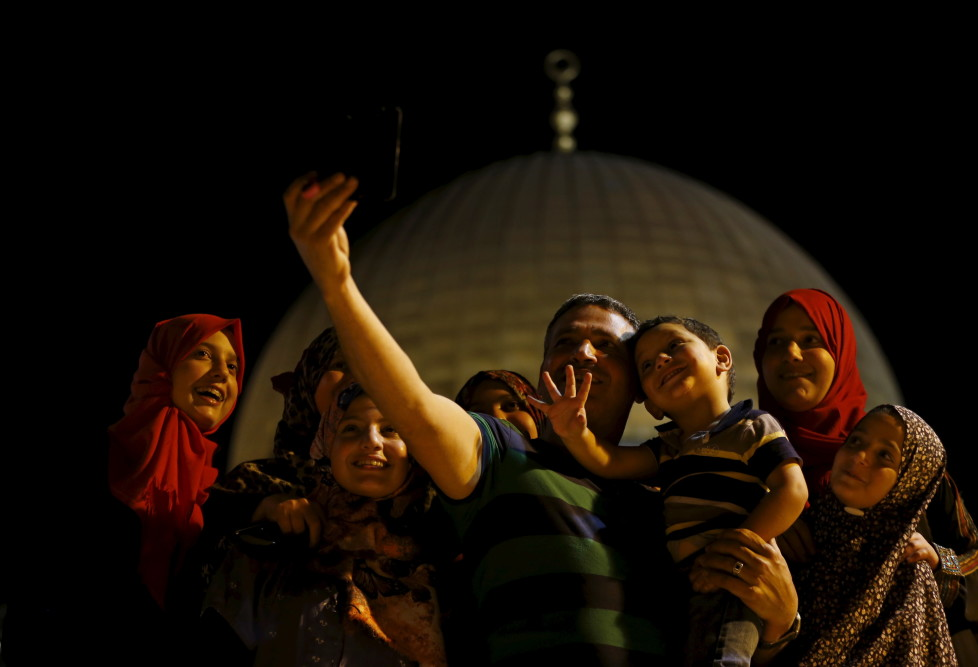 """Palestinian Dahud Hamad, 48, from the West Bank city of Hebron, takes a selfie photo with his family in front of the Dome of the Rock on the compound known to Muslims as the Noble Sanctuary and to Jews as Temple Mount, in Jerusalem's Old City, during the holy month of Ramadan, July 1, 2015. This is Hamad's second visit to the compound. Palestinians young and old have jumped on a trend for taking """"selfies"""" at Al Aqsa, the 8th century Muslim shrine in Jerusalem, both as a personal memento and for relatives prevented from or unable to visit the ancient compound. REUTERS/Ammar Awad PICTURE 15 OF 16 FOR WIDER IMAGE STORY """"SELFIES AT DOME OF THE ROCK"""" SEARCH """"SELFIE ROCK"""" FOR ALL PICTURES - RTX1JDHD"""