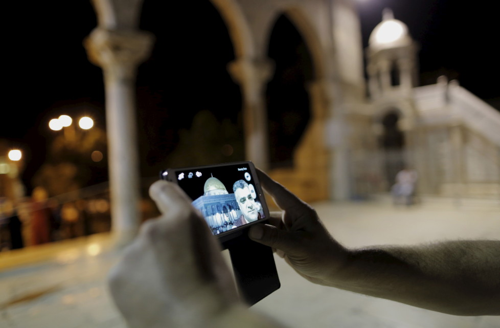 """Palestinian Dafer Kaloteer, 48, from Jerusalem, takes a selfie photo in front of the Dome of the Rock on the compound known to Muslims as Noble Sanctuary and to Jews as Temple Mount, in Jerusalem's Old City, during the holy month of Ramadan, July 4, 2015. Palestinians young and old have jumped on a trend for taking """"selfies"""" at Al Aqsa, the 8th century Muslim shrine in Jerusalem, both as a personal memento and for relatives prevented from or unable to visit the ancient compound. REUTERS/Ammar Awad PICTURE 14 OF 16 FOR WIDER IMAGE STORY """"SELFIES AT DOME OF THE ROCK"""" SEARCH """"SELFIE ROCK"""" FOR ALL PICTURES - RTX1JDHK"""