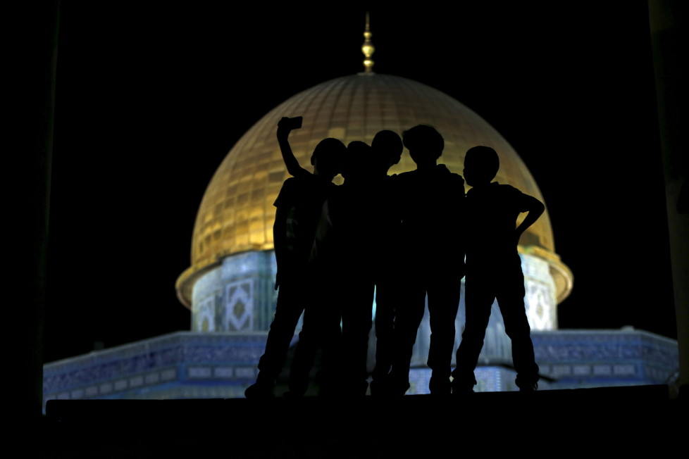 """Palestinian Ali Souwan, 12, from the West Bank city of Hebron, takes a selfie photo with his friends in front of the Dome of the Rock on the compound known to Muslims as Noble Sanctuary and to Jews as Temple Mount, in Jerusalem's Old City, during the holy month of Ramadan, July 4, 2015. Souwan said he has not been to Al Aqsa in three years, and that he took the selfie to show his friends and so that he'll have a souvenir. Palestinians young and old have jumped on a trend for taking """"selfies"""" at Al Aqsa, the 8th century Muslim shrine in Jerusalem, both as a personal memento and for relatives prevented from or unable to visit the ancient compound. REUTERS/Ammar Awad PICTURE 16 OF 16 FOR WIDER IMAGE STORY """"SELFIES AT DOME OF THE ROCK"""" SEARCH """"SELFIE ROCK"""" FOR ALL PICTURES - RTX1JDHM"""