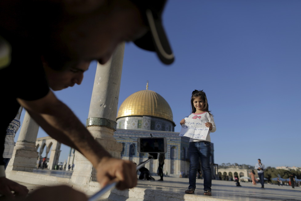 """Palestinian Shadi Etmezeh (L), 25, from the West Bank village of Idna, near Hebron, takes a photo of a relative holding a note reading: """"Muatasem Etmezeh the mosque misses you"""" in front of the Dome of the Rock on the compound known to Muslims as Noble Sanctuary and to Jews as Temple Mount, in Jerusalem's Old City, during the holy month of Ramadan, July 4, 2015. This is Etmezeh's first visit to the compound. Palestinians young and old have jumped on a trend for taking """"selfies"""" at Al Aqsa, the 8th century Muslim shrine in Jerusalem, both as a personal memento and for relatives prevented from or unable to visit the ancient compound. REUTERS/Ammar Awad PICTURE 9 OF 16 FOR WIDER IMAGE STORY """"SELFIES AT DOME OF THE ROCK"""" SEARCH """"SELFIE ROCK"""" FOR ALL PICTURES - RTX1JDHO"""