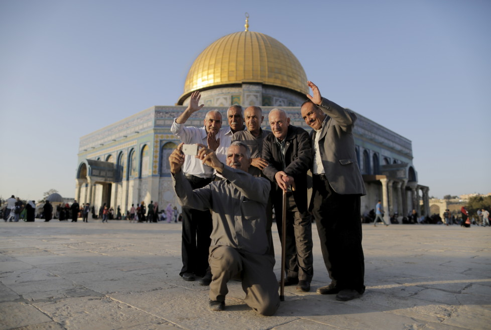 """Palestinian Hussam Abu Daba'a (C), 55, from the West Bank city of Hebron, takes a selfie photo with friends and relatives in front of the Dome of the Rock on the compound known to Muslims as Noble Sanctuary and to Jews as Temple Mount, in Jerusalem's Old City, during the holy month of Ramadan, July 1, 2015. This is Abu Daba'a's second visit to the compound. Palestinians young and old have jumped on a trend for taking """"selfies"""" at Al Aqsa, the 8th century Muslim shrine in Jerusalem, both as a personal memento and for relatives prevented from or unable to visit the ancient compound. REUTERS/Ammar Awad TPX IMAGES OF THE DAY PICTURE 10 OF 16 FOR WIDER IMAGE STORY """"SELFIES AT DOME OF THE ROCK"""" SEARCH """"SELFIE ROCK"""" FOR ALL PICTURES TPX IMAGES OF THE DAY - RTX1JDHR"""