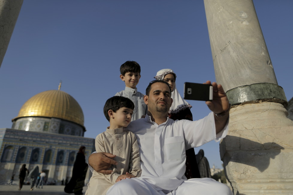 """Palestinian Muntasser Ne'erat, 31, from the West Bank city of Nablus, takes a selfie photo with his children in front of the Dome of the Rock on the compound known to Muslims as Noble Sanctuary and to Jews as Temple Mount, in Jerusalem's Old City, during the holy month of Ramadan, July 1, 2015. This is Ne'erat's first visit to the compound. Palestinians young and old have jumped on a trend for taking """"selfies"""" at Al Aqsa, the 8th century Muslim shrine in Jerusalem, both as a personal memento and for relatives prevented from or unable to visit the ancient compound. REUTERS/Ammar Awad PICTURE 12 OF 16 FOR WIDER IMAGE STORY """"SELFIES AT DOME OF THE ROCK"""" SEARCH """"SELFIE ROCK"""" FOR ALL PICTURES - RTX1JDHS"""