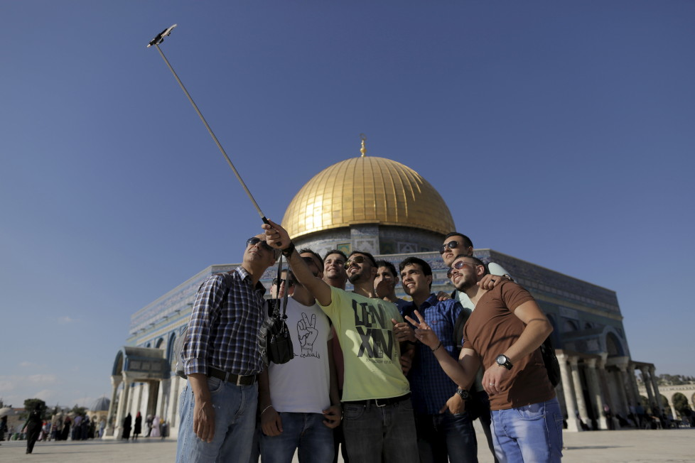"""Palestinian Hakem Shtayeh (C), 28, from the West Bank city of Nablus, takes a selfie photo with friends in front of the Dome of the Rock on the compound known to Muslims as Noble Sanctuary and to Jews as Temple Mount, in Jerusalem's Old City, during the holy month of Ramadan, June 29, 2015. This is Shtayeh's first visit to the compound. Palestinians young and old have jumped on a trend for taking """"selfies"""" at Al Aqsa, the 8th century Muslim shrine in Jerusalem, both as a personal memento and for relatives prevented from or unable to visit the ancient compound. REUTERS/Ammar Awad PICTURE 7 OF 16 FOR WIDER IMAGE STORY """"SELFIES AT DOME OF THE ROCK"""" SEARCH """"SELFIE ROCK"""" FOR ALL PICTURES - RTX1JDHX"""