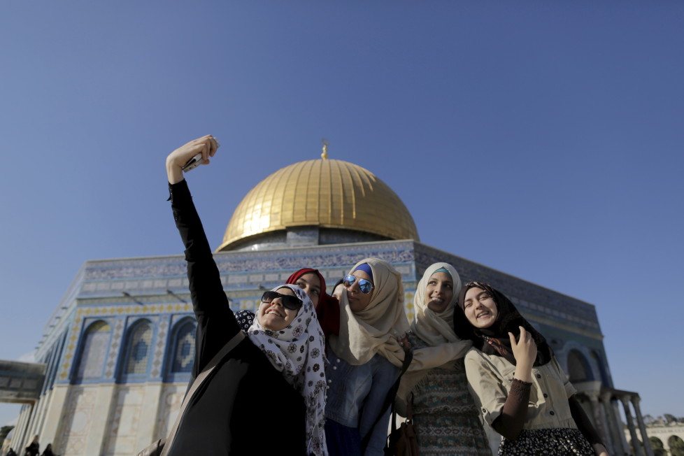 """Palestinian Sanaa Abu Jaudi (L), 16, from the West Bank city of Jenin, takes a selfie photo with friends in front of the Dome of the Rock on the compound known to Muslims as Noble Sanctuary and to Jews as Temple Mount, in Jerusalem's Old City, during the holy month of Ramadan, June 29, 2015. This is Abu Jaudi's third visit to the compound. Palestinians young and old have jumped on a trend for taking """"selfies"""" at Al Aqsa, the 8th century Muslim shrine in Jerusalem, both as a personal memento and for relatives prevented from or unable to visit the ancient compound. REUTERS/Ammar Awad TPX IMAGES OF THE DAY PICTURE 3 OF 16 FOR WIDER IMAGE STORY """"SELFIES AT DOME OF THE ROCK"""" SEARCH """"SELFIE ROCK"""" FOR ALL PICTURES TPX IMAGES OF THE DAY - RTX1JDHZ"""