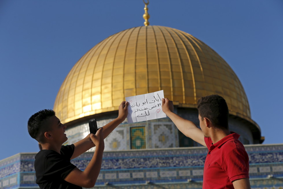 """Palestinian Ali Hassan (L), 16, from the West Bank city of Hebron, takes a photo of a note, reading """"Iyad Abu Reine the mosque misses you"""", in front of the Dome of the Rock on the compound known to Muslims as Noble Sanctuary and to Jews as Temple Mount, in Jerusalem's Old City, during the holy month of Ramadan, July 1, 2015. This is Hassan's second visit to the compound. Palestinians young and old have jumped on a trend for taking """"selfies"""" at Al Aqsa, the 8th century Muslim shrine in Jerusalem, both as a personal memento and for relatives prevented from or unable to visit the ancient compound. REUTERS/Ammar Awad PICTURE 2 OF 16 FOR WIDER IMAGE STORY """"SELFIES AT DOME OF THE ROCK"""" SEARCH """"SELFIE ROCK"""" FOR ALL PICTURES - RTX1JDI8"""