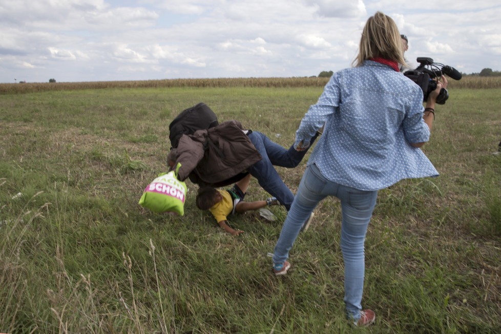 A migrant carrying a child falls after tripping on TV camerawoman (R) Petra Laszlo while trying to escape from a collection point in Roszke village, Hungary, September 8, 2015. Laszlo, a camerawoman for a private television channel in Hungary, was fired late on Tuesday after videos of her kicking and tripping up migrants fleeing police, including a man carrying a child, spread in the media and on the internet. REUTERS/Marko Djurica - RTX1RP8Z