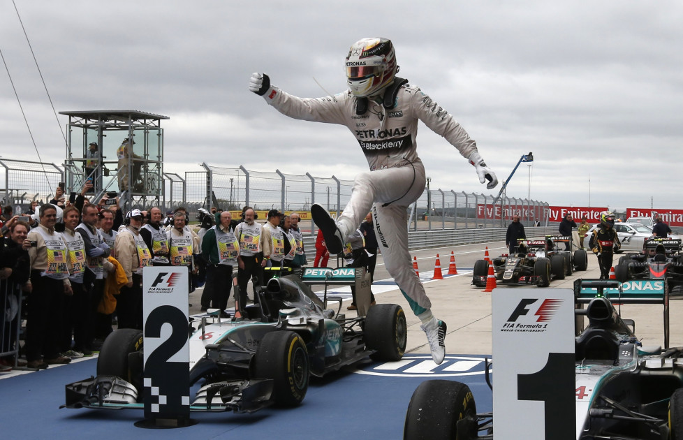 Mercedes Formula One driver Lewis Hamilton of Britain leaps off of his car after winning the U.S. F1 Grand Prix at the Circuit of The Americas in Austin, Texas October 25, 2015. Hamilton clinched his third Formula One world championship on Sunday after winning a thrilling and unpredictable U.S. Grand Prix for Mercedes. REUTERS/Adrees Latif (TPX IMAGES OF THE DAY) - RTX1T6W5