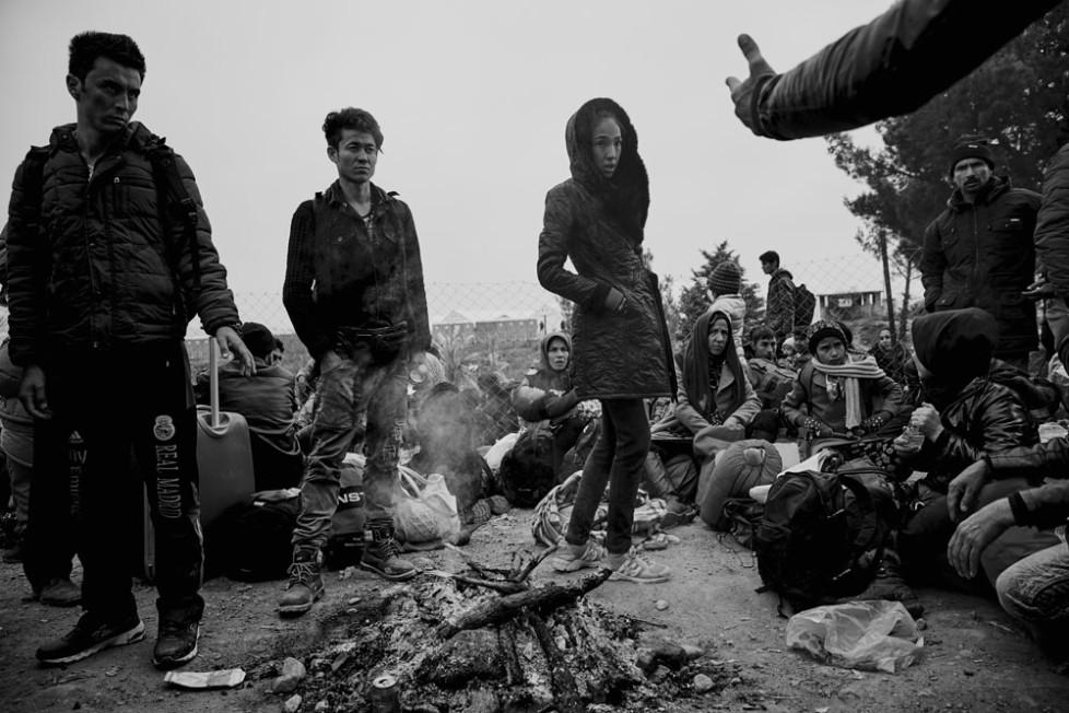 Flüchtlinge die im Camp in Idomeni festsitzen , wenn sie nicht aus Syrien, Afgahnistan oder dem Irak stammen . Eine Gruppe junger Menschen ist um ein Feuer versammelt. Alles was brennbar ist , wird angezündet um Kleider zu trocknen und etwas warm zu haben .