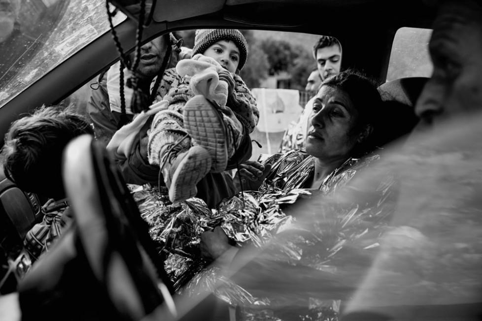 Flüchtlinge , die eben auf Lesbos von der Türkei angekommen sind . Frauen und Kinder werden falls möglich zum nächstgelegenen Camp gefahren . Die Männer müssen meistens zu Fuss gehen . Einer Mutter wird Ihr Kind von einem freiwilligen Helfer ins Auto gereicht .