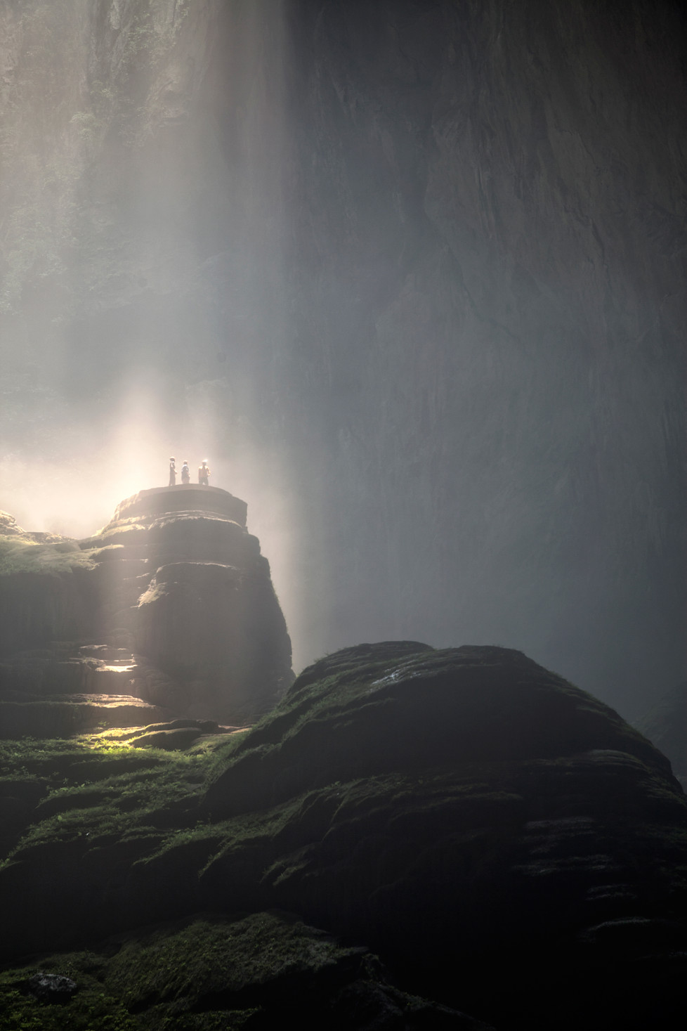 Drei Caver in den Sonnenstrahlen in der ersten Doline in Son Doong Cave. Foto: Tanja Demarmels