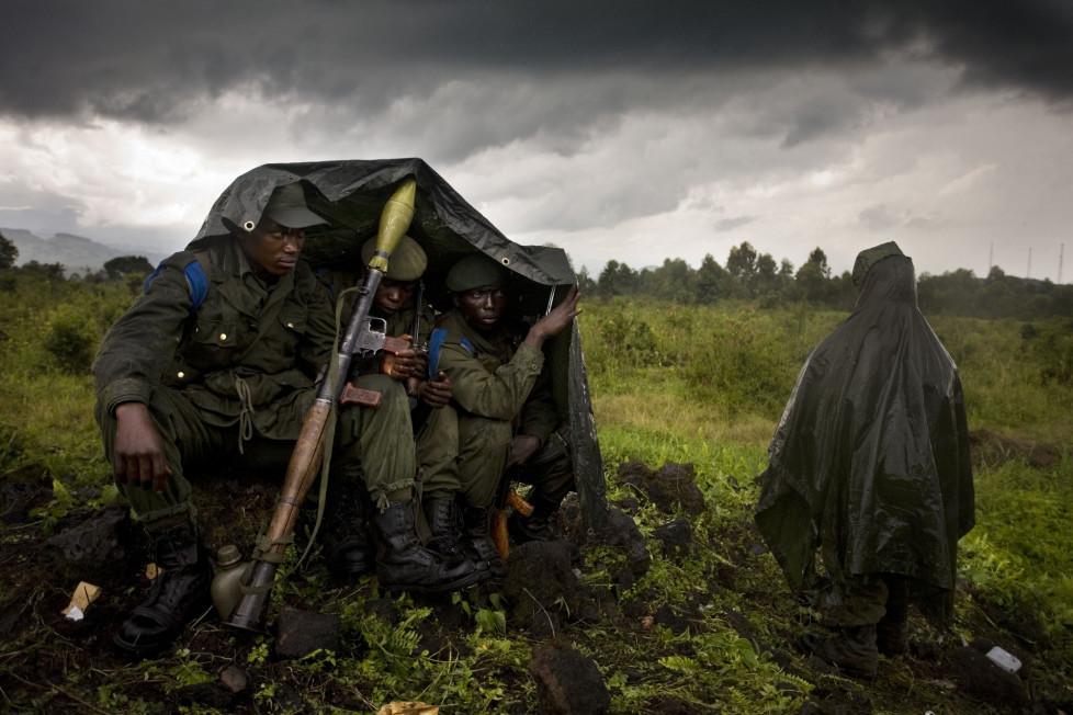 Kongolesische Soldaten schützen sich in fünf Kilometer Entfernung von der Frontlinie unter Plachen vor dem Regen.
