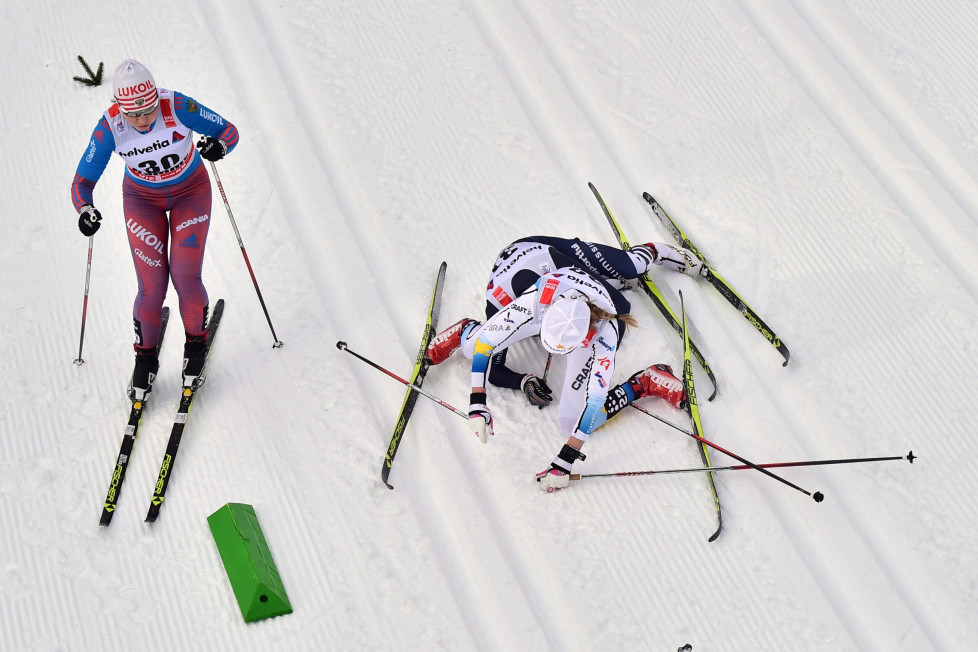"""Swedish Maria Rydqvist (top R) falls with Italian Lucia Scardoni (bottom R) next to Russian Alisa Zhambalova during the women's 10 km Mass Start classic competition of the """"Tour de Ski"""" Cross Country World Cup on January 9, 2016 in the Lake Tesrero track of Val Di Fiemme. / AFP / GIUSEPPE CACACE"""