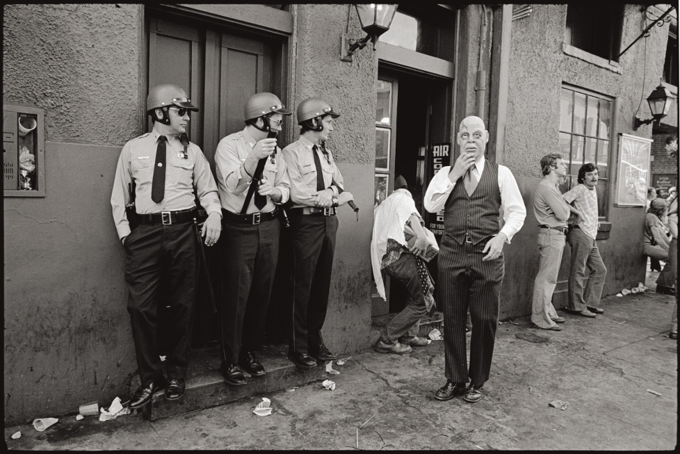 USA. New Orleans, Louisiana. 1977. Mardi Gras. Police and masked man in the French Quarter.