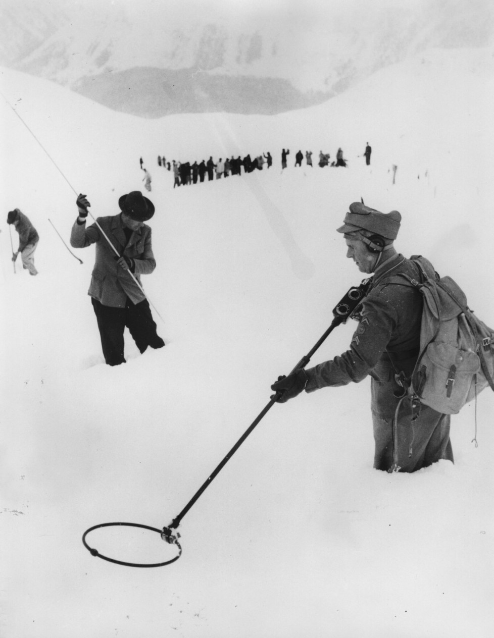 4th January 1956: Six winter sports enthusiasts were buried by an avalanche on the famous Parsenn ski trail. Two of the men were rescued, three others including a woman were killed. Here a Swiss soldier uses a metal detector in the hopes that he may get a lead on the whereabouts of the missing man, Richard Jackson of California. (Photo by Hulton Archive/Getty Images)