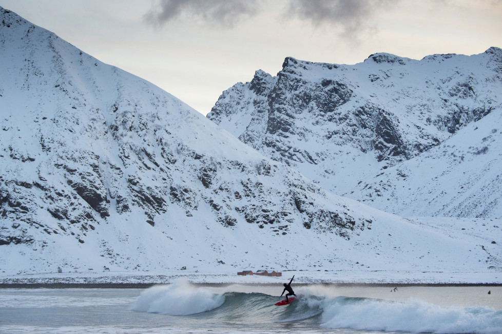 A surfer rides a wave at the snowy beach of Unstad, in Lofoten Island, Arctic Circle, on March 9, 2016. Surfers from all over the world comes to Lofoten island to surf in extrem conditions. Ocean temperature is 6-7 °C, air temperature around 0°C in spite of a weather very unstable. / AFP / OLIVIER MORIN