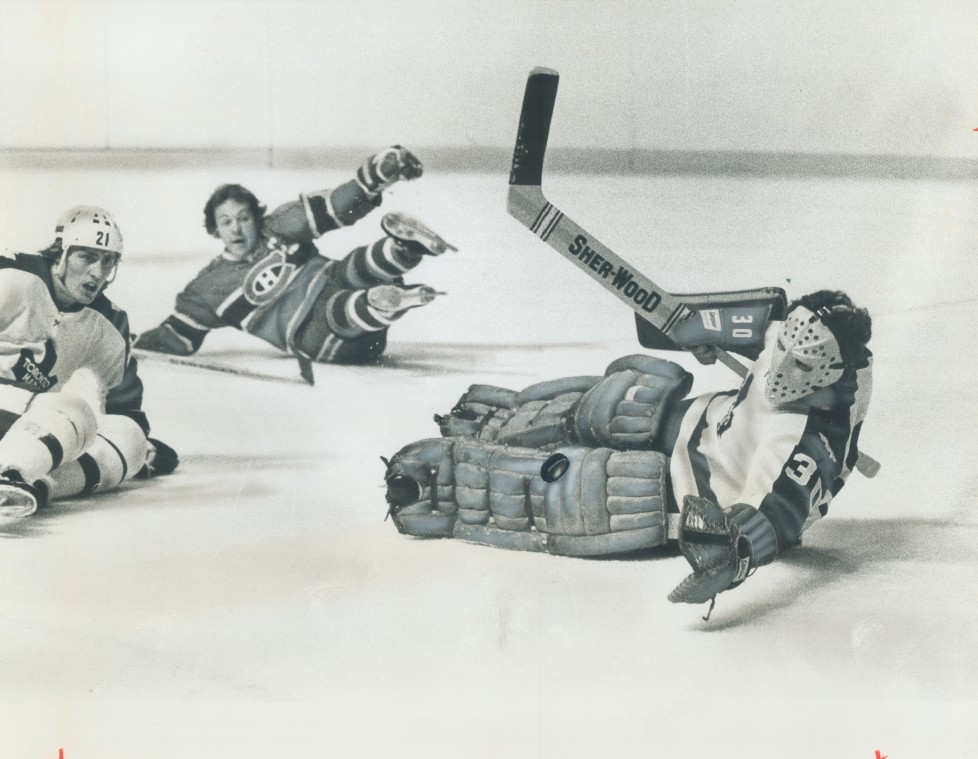 CANADA - NOVEMBER 23: Dazzling glove save is made by Leaf goalie Wayne Thomas as Montreal Canadiens' Yvan Cournoyer; also sprawled on ice; looks on with astonishment. Action occured in National Hockey League game at Gardens Saturday night between long-time rivals. Thomas played fine game; but Habs' defensive work led to 4-2 loss. Leafs salvaged point from weekend; trying Boston Bruins; 3-3 last night. (Photo by Dick Darrell/Toronto Star via Getty Images)