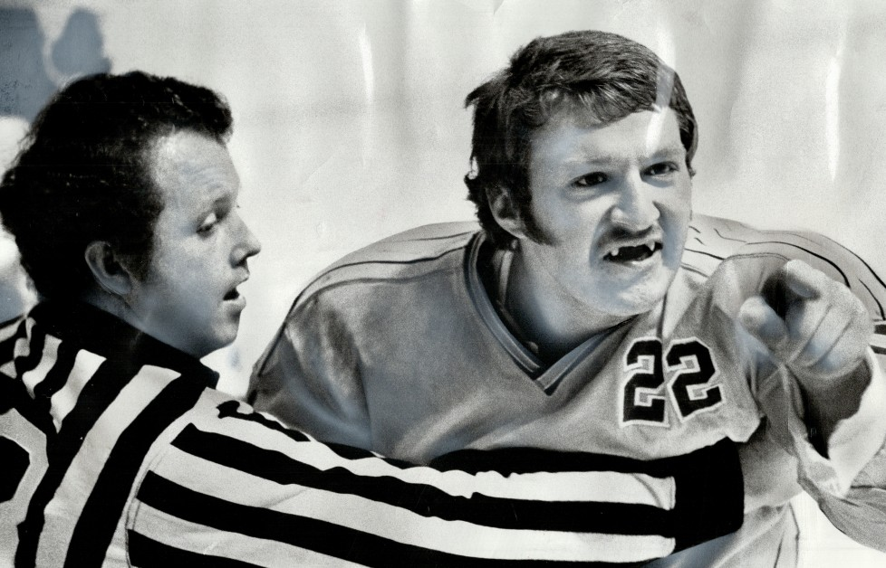 CANADA - MAY 01: Baring his fangs: Chicago Cougars' Jim Benzelock snarls his defiance at Toronto Toro opponent as linesman Mike Entwistle attempts to restrain him during one of many brawls that World Hockey Association semi-final Gardens. Toros won; 5-3; to take series; but not before wild third period that in two 10-minute misconducts and pair of fight majors. Toro's edge in skating was the difference. [Incomplete] (Photo by Doug Griffin/Toronto Star via Getty Images)