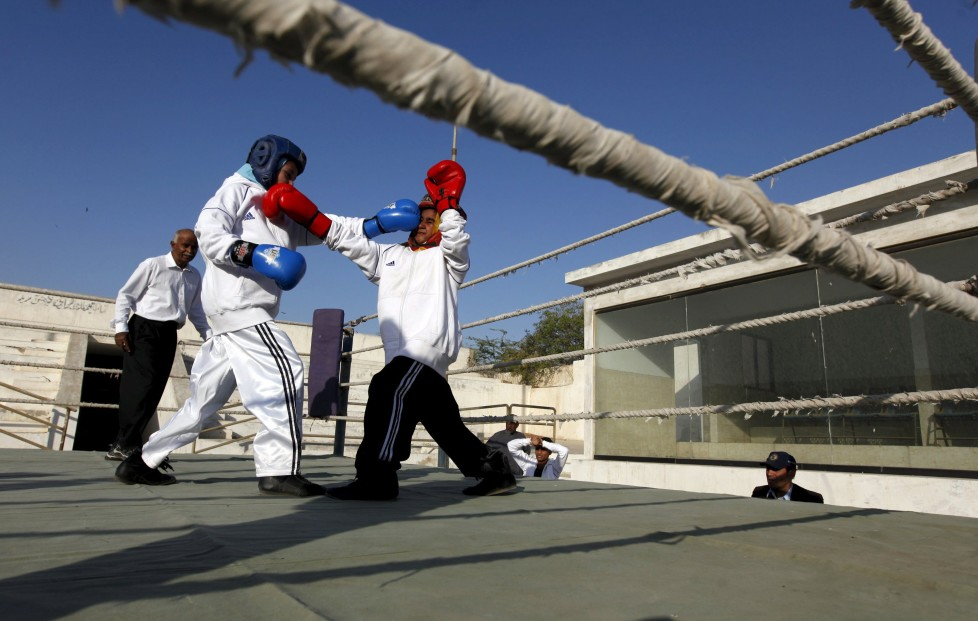 "Tabia (L), 12, fights against Aamna, 11, during the Sindh Junior Sports Association Boxing Tournament in Karachi, Pakistan February 21, 2016. For the past six months about a dozen girls, aged 8 to 17, have gone to the Pak Shine Boxing Club after school to practice their jabs, hooks and upper cuts. Pakistani women have been training as boxers in small numbers and competed in the South Asian Games last year, said Younis Qambrani, the coach who founded the club in 1992 in the Karachi neighbourhood of Lyari, better known for internecine gang warfare than for breaking glass ceilings. REUTERS/Akhtar Soomro SEARCH ""THE WIDER IMAGE"" FOR ALL STORIES"