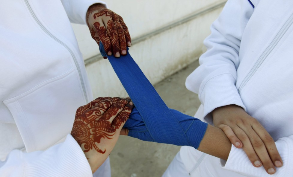 "A friend wraps the hand of a boxer competing in the Sindh Junior Sports Association Boxing Tournament in Karachi, Pakistan February 21, 2016. For the past six months about a dozen girls, aged 8 to 17, have gone to the Pak Shine Boxing Club after school to practice their jabs, hooks and upper cuts. Pakistani women have been training as boxers in small numbers and competed in the South Asian Games last year, said Younis Qambrani, the coach who founded the club in 1992 in the Karachi neighbourhood of Lyari, better known for internecine gang warfare than for breaking glass ceilings. REUTERS/Akhtar Soomro SEARCH ""THE WIDER IMAGE"" FOR ALL STORIES"