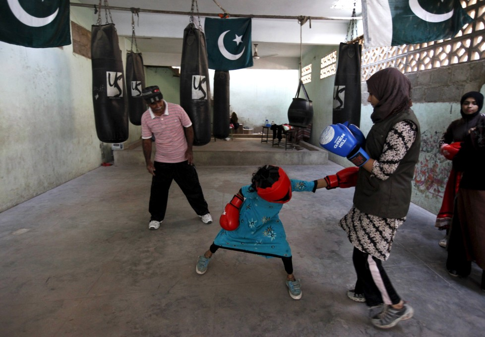 "REFILE - CLARIFYING NAME OF BOXING CLUBArisha, 9, punches Misbah during an exercise session at the first women's boxing coaching camp in Karachi, Pakistan February 20, 2016. For the past six months about a dozen girls, aged 8 to 17, have gone to the Pak Shaheen Boxing Club after school to practice their jabs, hooks and upper cuts. Pakistani women have been training as boxers in small numbers and competed in the South Asian Games last year, said Younis Qambrani, the coach who founded the club in 1992 in the Karachi neighbourhood of Lyari, better known for internecine gang warfare than for breaking glass ceilings. REUTERS/Akhtar Soomro SEARCH ""THE WIDER IMAGE"" FOR ALL STORIES"
