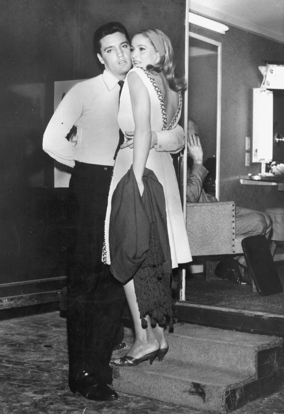 ZUM 80. GEBURTSTAG DER SCHWEIZER FILMSCHAUSPIELERIN URSULA ANDRESS AM SAMSTAG, 19. MAERZ 2016, STELLEN WIR IHNEN FOLGENDES BILDMATERIAL ZUR VERFUEGUNG - Elvis Presley und die um einen Kopf kleinere Schweizer Schauspielerin Ursula Andress finden hinter den Kulissen in einem Hollywood-Studio aller Groessenunterschiede zum Trotz einen Weg, um sich auf gemeinsamer Basis naeherzukommen (Archivbild von 1963). Die beiden standen zuvor im Film 'Fun in Acapulco' zusammen vor der Kamera. Am 16. August 1997 jaehrt sich der Todestag von Elvis Presley zum 20. Mal. (KEYSTONE/Str)