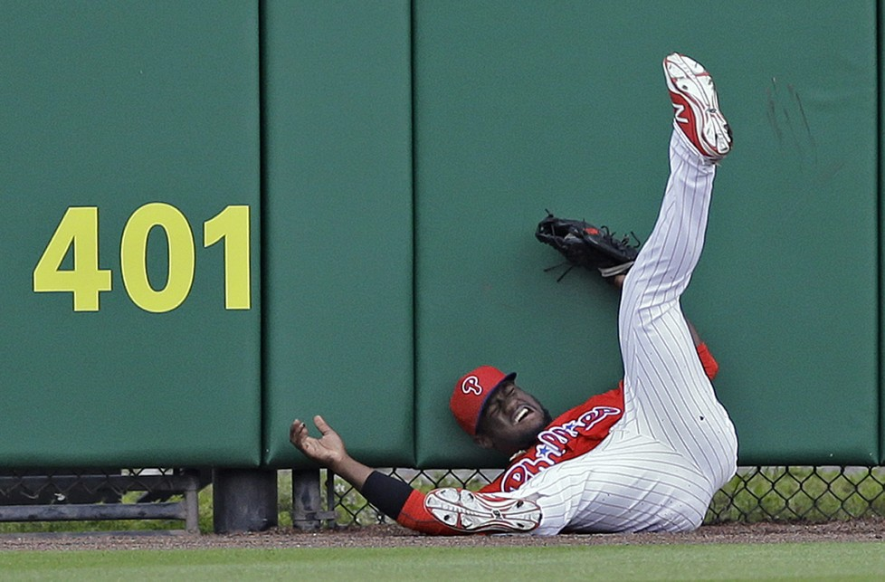 Philadelphia Phillies center fielder Odubel Herrera crashes into the wall chasing down a fly out by Toronto Blue Jays' Kevin Pillar during the first inning of a spring training baseball game Friday, March 25, 2016, in Clearwater, Fla. (AP Photo/Chris O'Meara)