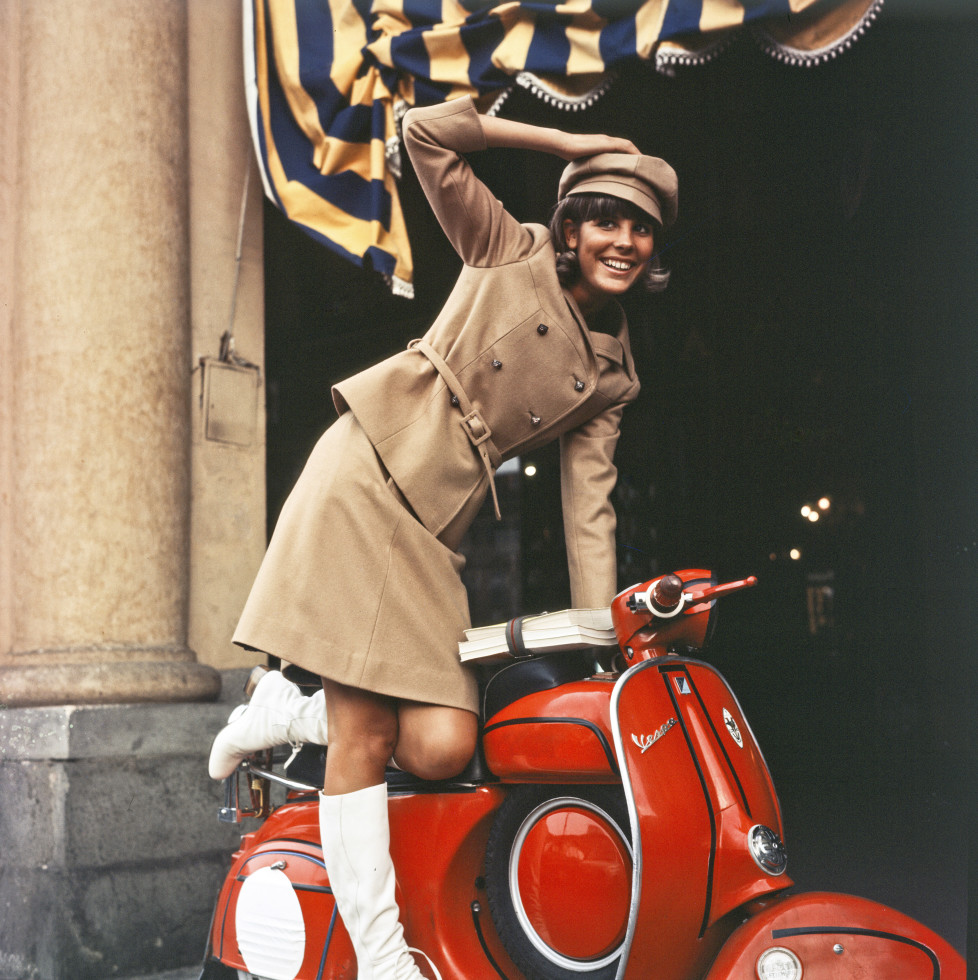Cheerful portrait of Marisa Sannia who smiles while resting in balance on a red Piaggio Vespa; the Sardinian singer-songwriter wears a typical Sixties' outfit, composed by white boots, a velvet suede suit and a postman hat ton-sur-ton. Italy, 1966. (Photo by Mondadori Portfolio via Getty Images)