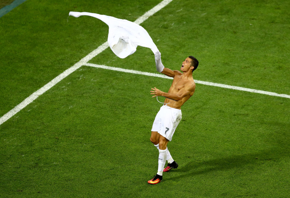 MILAN, ITALY - MAY 28: Cristiano Ronaldo of Real Madrid takes off his shirt in celebration after scoring the winning penalty in the penalty shoot out during the UEFA Champions League Final match between Real Madrid and Club Atletico de Madrid at Stadio Giuseppe Meazza on May 28, 2016 in Milan, Italy. (Photo by Clive Mason/Getty Images)