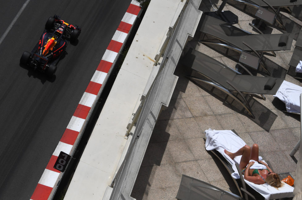 Infiniti Red Bull racing's Belgian-Dutch driver Max Verstappen drives as a woman sunbathes during the first practice session at the Monaco street circuit, on May 26, 2016 in Monaco, three days ahead of the Monaco Formula 1 Grand Prix. / AFP PHOTO / PASCAL GUYOT