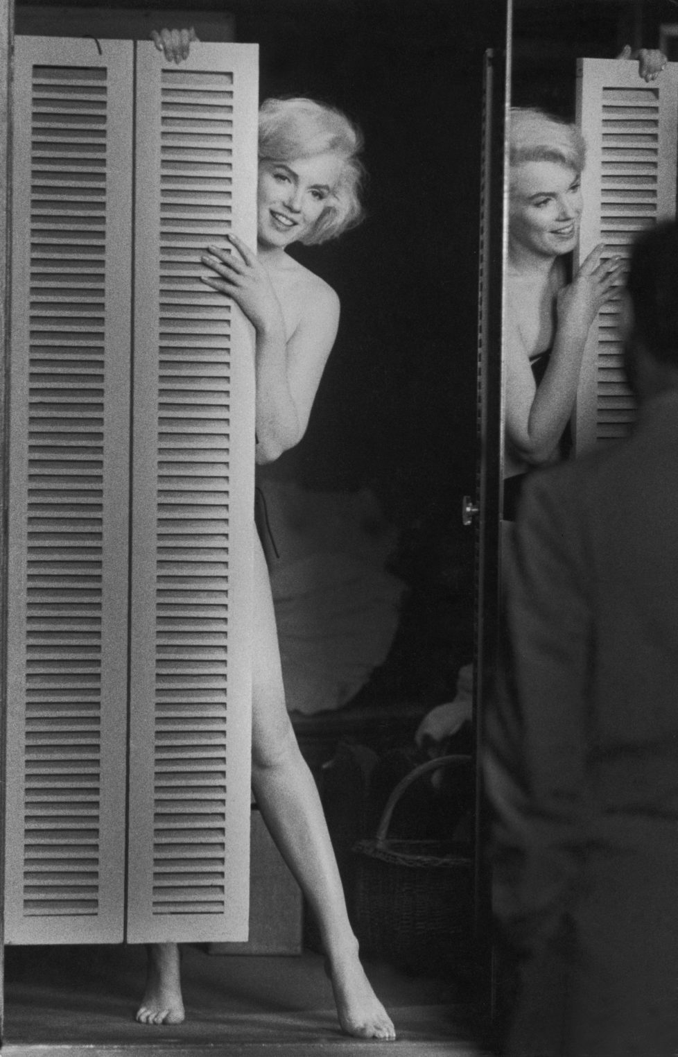 Actress Marilyn Monroe peering out at her husband Arthur Miller fr. behind door after putting on sexy bikini bathing suit she purchased, w. the price tag still on it, to see if he approves, at studio after work on movie Let's Make Love. (Photo by John Bryson/The LIFE Images Collection/Getty Images)