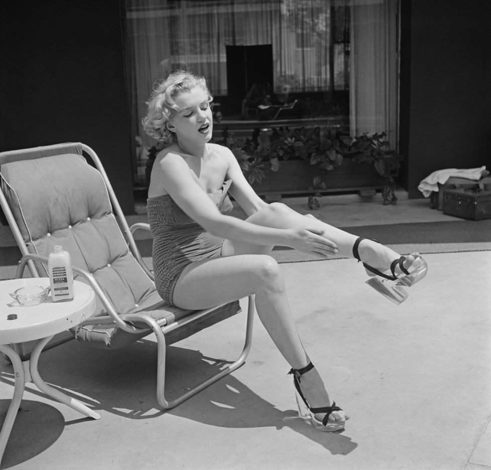 American actress Marilyn Monroe (1926 - 1962) applies Nivea lotion to her legs, circa 1951. (Photo by Archive Photos/Getty Images) *** Local Caption *** Marilyn Monroe