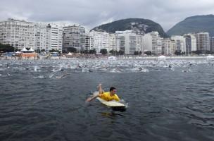 ZUM COUNTDOWN VON 100 TAGEN BIS ZUR EROEFFNUNGSZEREMONIE DER OLYMPISCHEN SOMMERSPIELE RIO 2016 AM MITTWOCH, 27. APRIL 2016, STELLEN WIR IHNEN FOLGENDES BILDMATERIAL ZUR VERFUEGUNG -  A lifeguard paddles along participants of the annual Travessia dos Fortes or Fort Crossing swimming competition in Copacabana Beach in Rio de Janeiro, Brazil, Sunday April 3, 2011. About 2,000 swimmers took part in the 2.08 mile aquatic marathon between Fort Copacabana and Fort Rudder. (KEYSTONE/AP Photo/Victor R. Caivano)