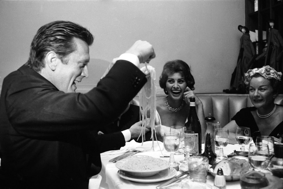 American actor Kirk Douglas serves himself a mound of spaghetti as Italian film producer Carlo Ponti (obscured), his wife, Italian actor Sophia Loren, and an unidentified woman in a pearl necklace watch and laugh, New York, New York, June 1958. (Photo by Peter Stackpole/The LIFE Picture Collection/Getty Images)