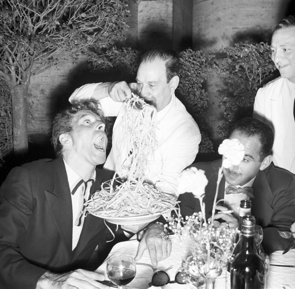 American actor Burt Lancaster sitting at the table of the restaurant Alfredo and pretending to eat fettuccine straight from Italian chef Alfredo Di Lelio's hands. Rome, 1959 (Photo by Franco Fedeli/Reporters Associati & Archivi/Mondadori Portfolio via Getty Images)