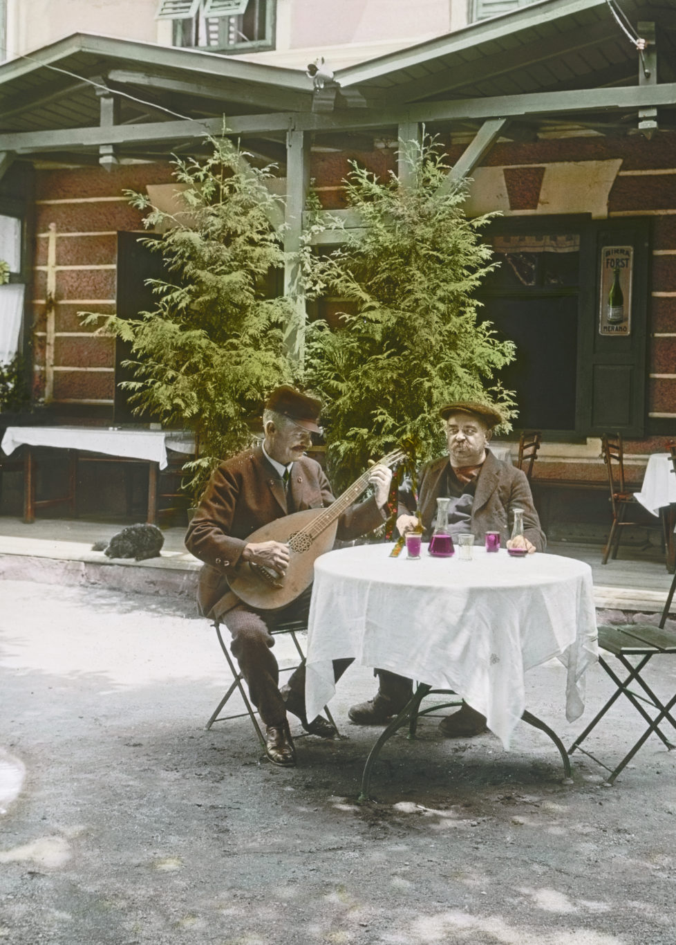 South Tyrol. Italy: Two revelers, with a mandolin, in front of a South Tyrolean Restaurant. about 1925. Handcolored lantern slide. (Photo by Imagno/Getty Images) S?dtirol. Italien: Zwei Zecher, einer mit Mandoline, vor einem S?dtiroler Gasthaus. Um 1925. Handkoloriertes Glasdiapositiv. *** Local Caption *** *** Local Caption ***