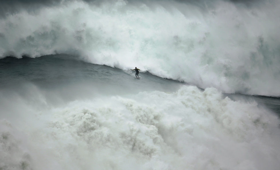 Big-wave surfer Garrett McNamara of the U.S. drops in on a large wave at Praia do Norte, in Nazare November 1, 2013. McNamara, who lives in Haleiwa, Hawaii, won the Biggest Wave title at the 2012 Billabong XXL Big Wave Awards with his world record 78-foot (24-metre) wave ridden at Praia do Norte, Nazare, Portugal on November 1, 2011. McNamara has returned to Nazare because he wants to try to beat the record again. REUTERS/Rafael Marchante (PORTUGAL - Tags: SPORT TPX IMAGES OF THE DAY) - RTX14WNV