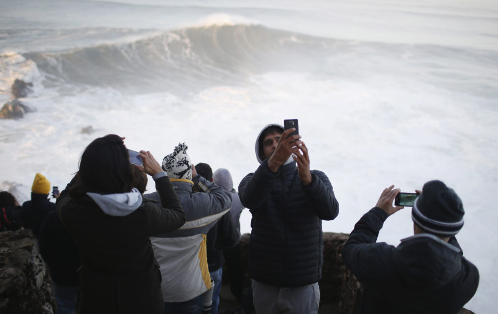 People gather to watch a tow-in surfing session at Praia do Norte, in Nazare December 11, 2014. Praia do Norte beach has gained popularity with big wave surfers since Hawaiian surfer Garrett McNamara broke a world record for the largest wave surfed here in 2011. REUTERS/Rafael Marchante (PORTUGAL - Tags: SPORT ENVIRONMENT) - RTR4HOLD